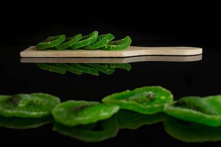 Group of nine slices of sweet green candied kiwifruit on small wooden cutting board isolated on black glass