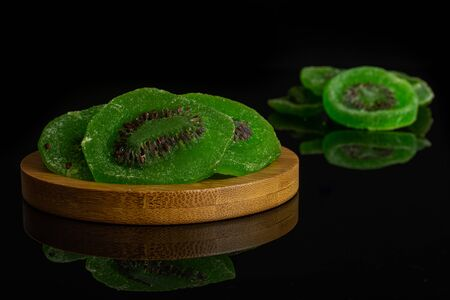 Group of seven slices of sweet green candied kiwifruit on bamboo coaster isolated on black glass