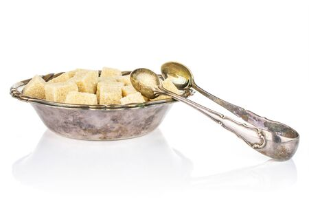 Lot of whole sweet brown sugar cube in metal bowl with sugar tongs isolated on white background