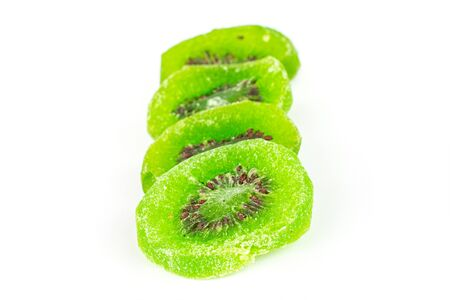 Group of four slices of sweet green candied kiwifruit isolated on white background Banco de Imagens