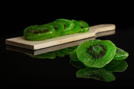 Group of eight slices of sweet green candied kiwifruit on small wooden cutting board isolated on black glass Banco de Imagens