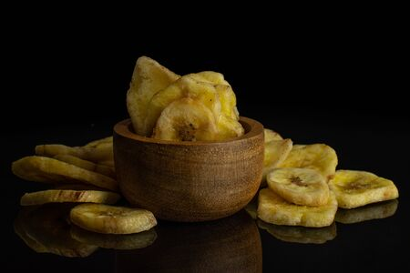 Lot of slices of sweet yellow dry banana in tiny wooden bowl isolated on black glass