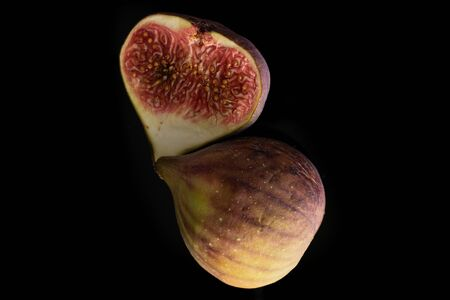 One half of fresh fig fruit flatlay isolated on black glass