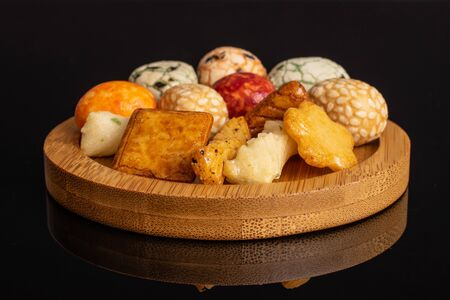 Lot of whole rice japan assortment on round bamboo coaster isolated on black glass