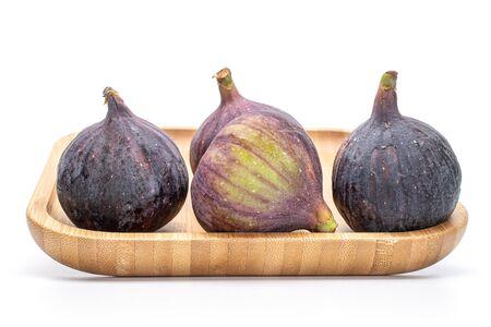 Group of three whole ripe fresh fig fruit on bamboo plate isolated on white background