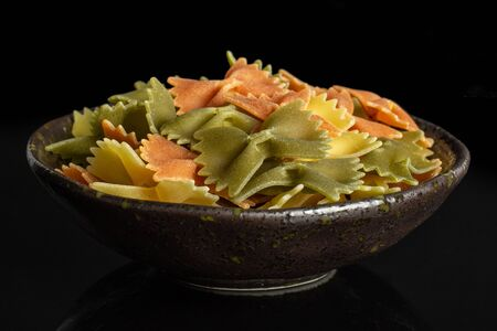 Lot of whole red, yellow and green uncooked farfalle in dark ceramic bowl isolated on black glass
