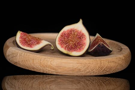 Group of one half two slices of fresh fig fruit on bamboo plate isolated on black glass