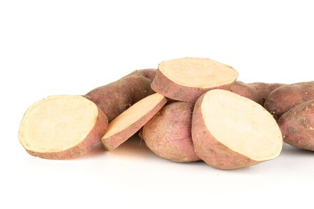 Lot of slices of fresh brown sweet potato isolated on white background