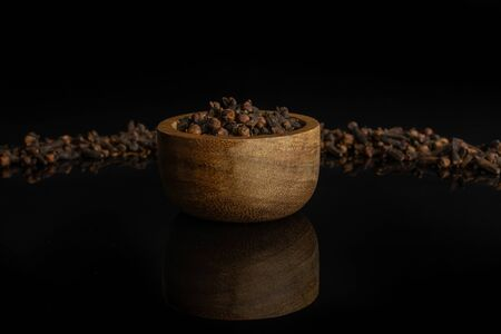 Lot of whole dry brown clove in tiny wooden bowl isolated on black glass