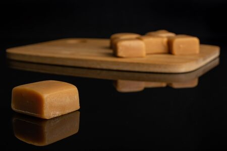 Group of six whole sweet golden caramel candy one is aside and the rest is on bamboo cutting board isolated on black glass 写真素材