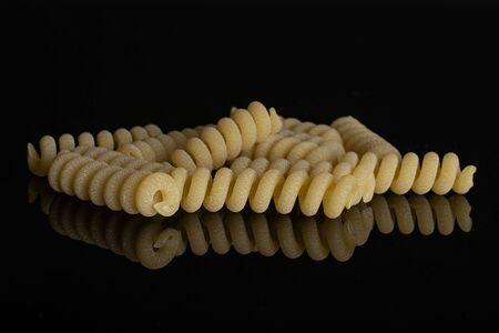 Lot of whole fresh raw pasta fusilli bucati isolated on black glass