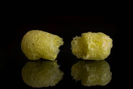 Group of two halves of salted yellow corn puff isolated on black glass