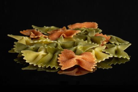 Lot of whole red, yellow and green uncooked farfalle isolated on black glass 写真素材