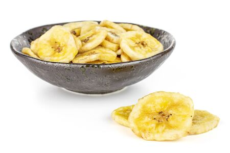 Lot of slices of sweet yellow dry banana in dark ceramic bowl isolated on white background