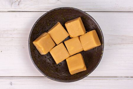 Group of seven whole sweet golden caramel candy in dark ceramic bowl flatlay on white wood 写真素材