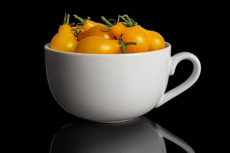 Lot of whole fresh yellow pear tomato in white ceramic cup isolated on black glass 写真素材
