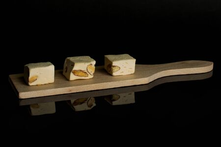 Group of three whole sweet white nougat on small wooden cutting board isolated on black glass 写真素材