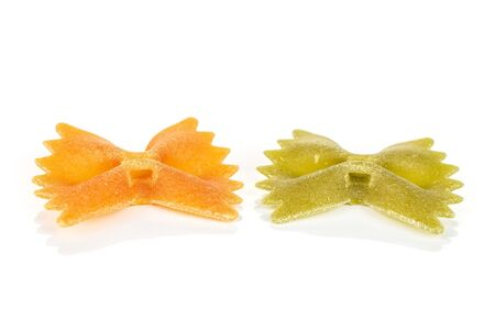 Group of two whole red and green uncooked farfalle isolated on white background
