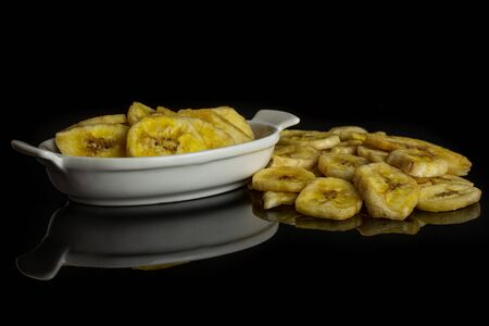 Lot of slices of sweet yellow dry banana in white oval ceramic bowl isolated on black glass