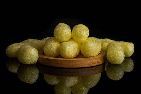 Lot of whole salted yellow corn puff on bamboo coaster isolated on black glass