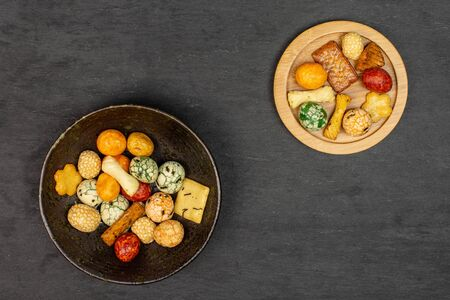 Lot of whole rice japan assortment on round bamboo coaster in dark ceramic bowl flatlay on grey stone 写真素材