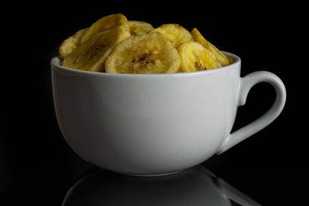 Lot of slices of sweet yellow dry banana in white ceramic cup isolated on black glass