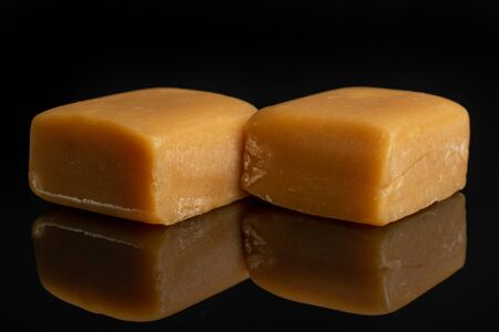 Group of two whole sweet golden caramel candy isolated on black glass