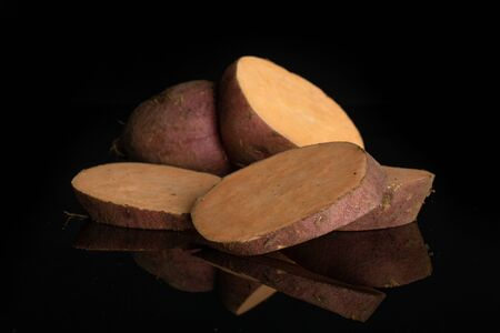 Group of one half three slices of fresh brown sweet potato isolated on black glass