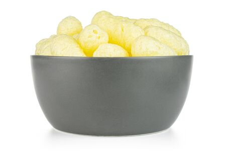 Lot of whole salted yellow corn puff in gray ceramic bowl isolated on white background
