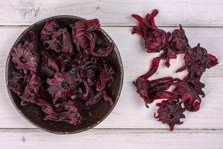 Lot of whole sweet red candied hibiscus in dark ceramic bowl flatlay on white wood 写真素材