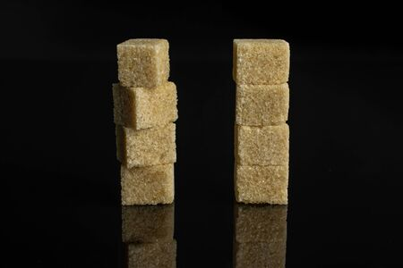 Group of eight whole sweet brown sugar cube isolated on black glass 写真素材