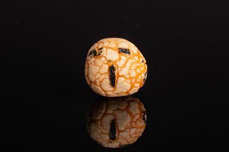 One whole orange rice japan assortment isolated on black glass