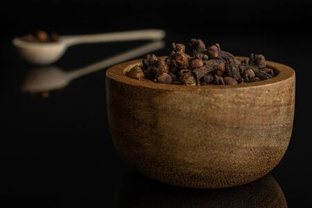 Lot of whole dry brown clove in tiny wooden bowl in a wooden spoon isolated on black glass 写真素材