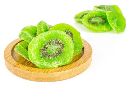 Lot of slices of sweet green candied kiwifruit on bamboo coaster isolated on white background