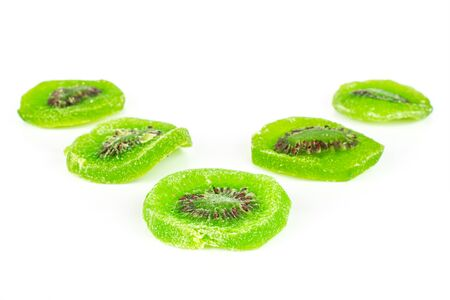 Group of five slices of sweet green candied kiwifruit isolated on white background