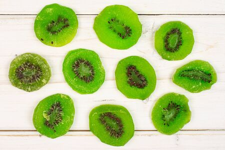 Group of ten slices of sweet green candied kiwifruit flatlay on white wood