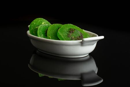Group of four slices of sweet green candied kiwifruit in white oval ceramic bowl isolated on black glass Banco de Imagens