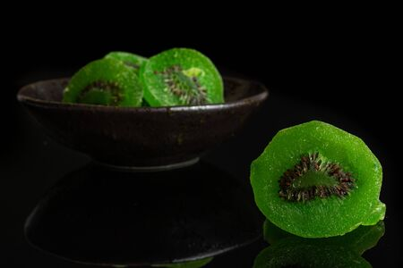 Group of four slices of sweet green candied kiwifruit in dark ceramic bowl isolated on black glass Banco de Imagens