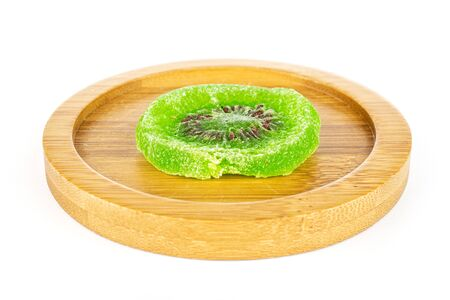 One slice of sweet green candied kiwifruit on bamboo coaster isolated on white background