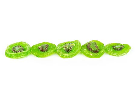 Group of five slices of sweet green candied kiwifruit in row isolated on white background