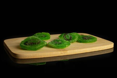 Group of five slices of sweet green candied kiwifruit on bamboo cutting board isolated on black glass