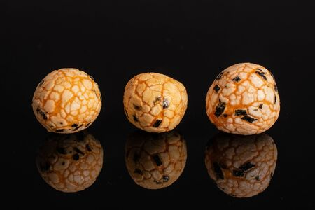 Group of three whole orange rice japan assortment isolated on black glass