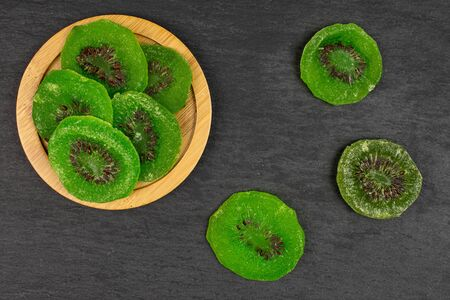 Group of eight slices of sweet green candied kiwifruit on bamboo coaster flatlay on grey stone
