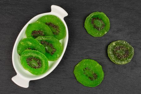 Group of eight slices of sweet green candied kiwifruit in white oval ceramic bowl flatlay on grey stone