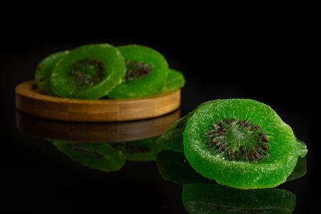 Group of four slices of sweet green candied kiwifruit on bamboo coaster isolated on black glass Banco de Imagens