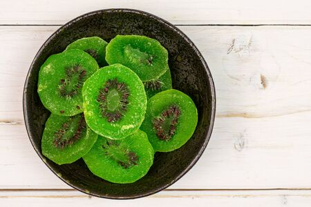 Lot of slices of sweet green candied kiwifruit in dark ceramic bowl flatlay on white wood