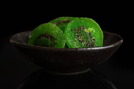Group of three slices of sweet green candied kiwifruit in dark ceramic bowl isolated on black glass