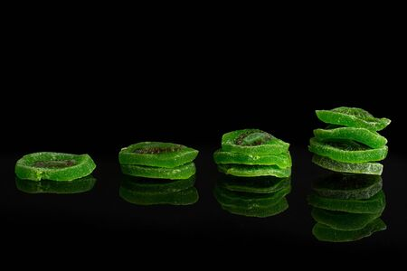 Group of ten slices of sweet green candied kiwifruit isolated on black glass