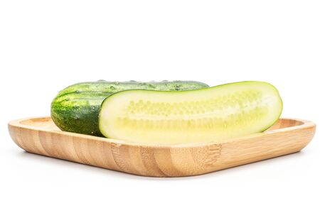 Group of one whole one half of fresh green pickling cucumber on wooden square plate isolated on white background