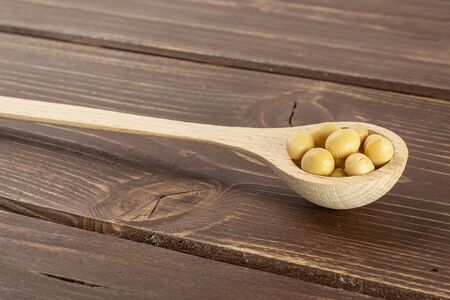Lot of whole raw yellow soya bean with wooden spoon on brown wood